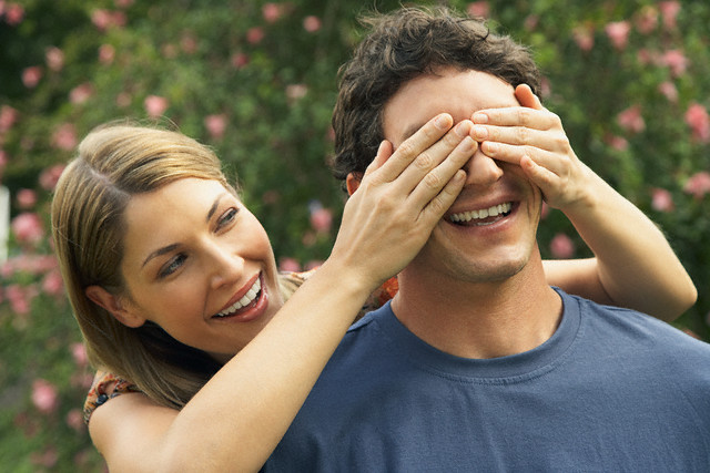 Wife covering her husband's eyes --- Image by © HBSS/Corbis